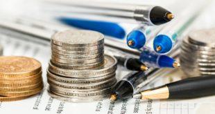Monety wśród długopisów i ołówków