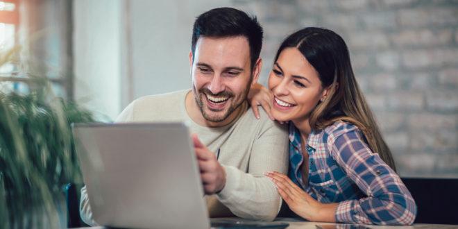 Uśmiechnięta para korzysta z laptopa