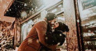 zakochana para obejmująca się zimą przed budynkiem