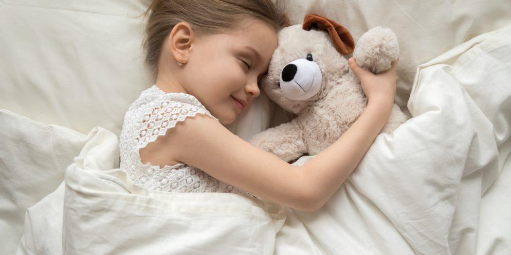 dziewczynka śpiąca z misiem na wygodnym materacu