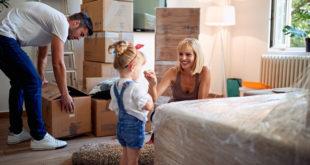 szczęśliwa rodzina zajmująca się pakowaniem rzeczy w sypialni do kartonów