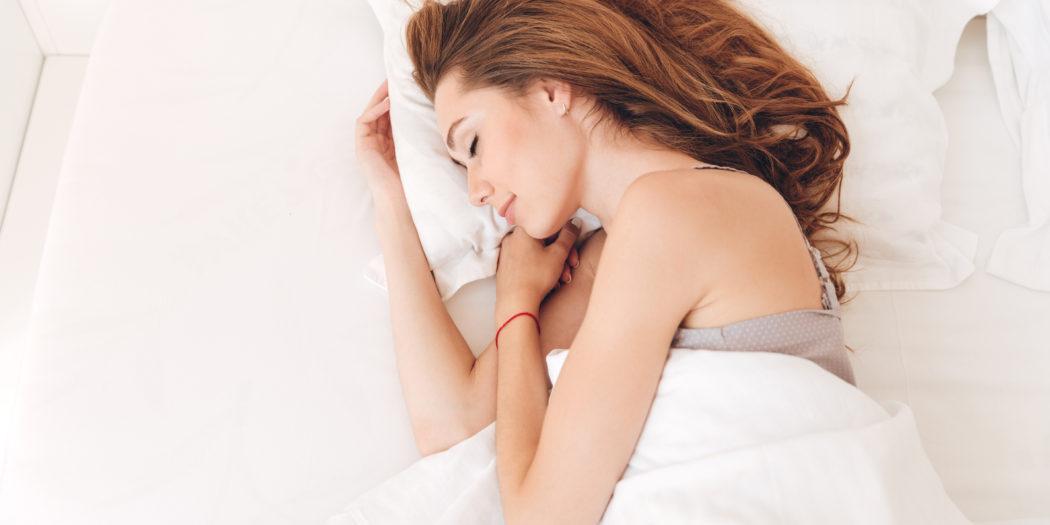 uśmiechnięta rudowłosa kobieta śpiąca w łóżku w białej pościeli