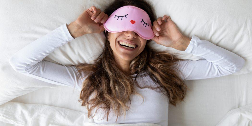 wyspana kobieta w łóżku z zabawną opaską na oczach