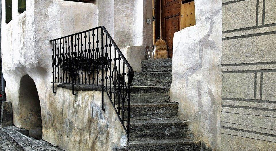 Kamienne schody zewnętrzne z metalową balustradą