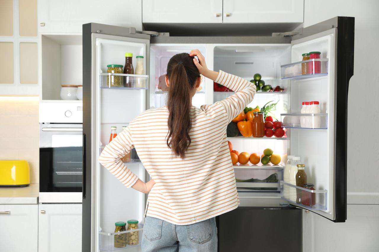 Kobieta zastanawia się, jaką lodówkę kupić do swojego mieszkania
