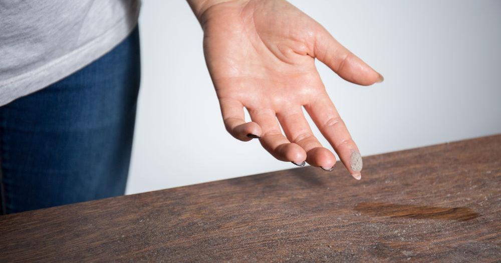 kobieta z palcem ubrudzonym kurzem