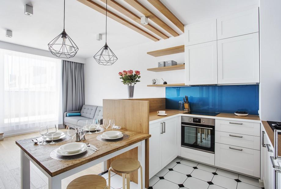 Nowoczesna biała kuchnia wykończona drewnianymi elementami