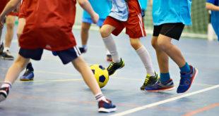 chłopcy grający w piłkę na sali gimnastycznej