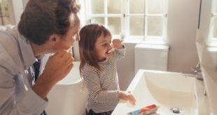 dziewczynka myjąca zęby z tatą
