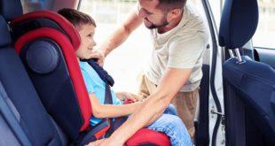 mężczyna wkłądający dziecko do fotelika samochodowego