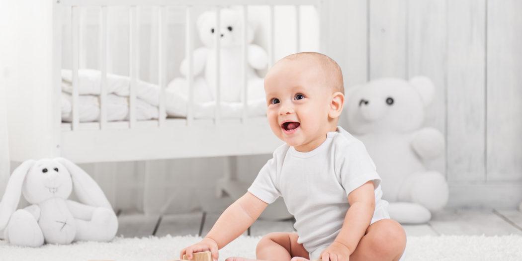siedzący niemowlak bawiący się klockami