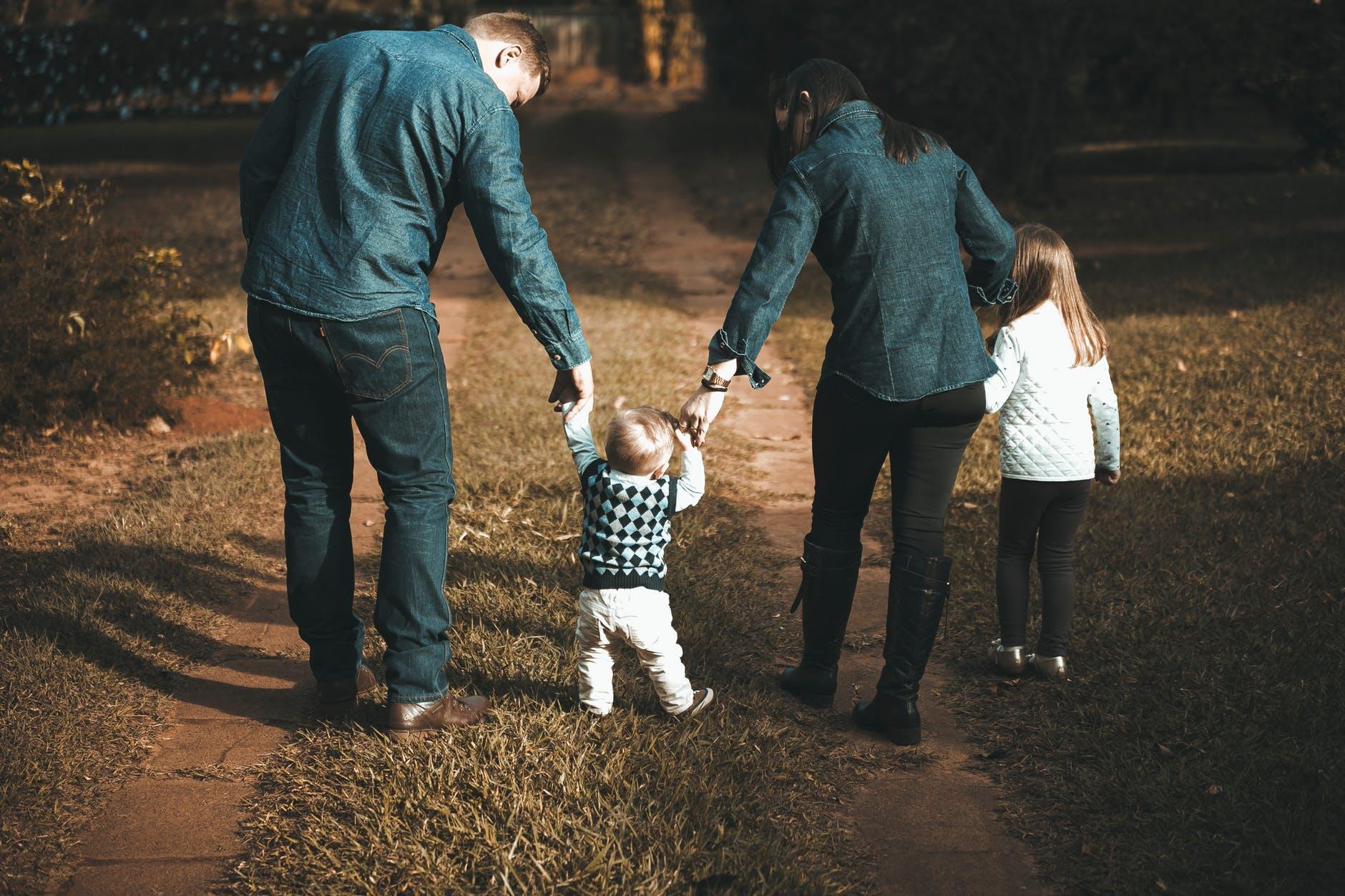 dwójka małych dzieci na spacerze z rodzicami