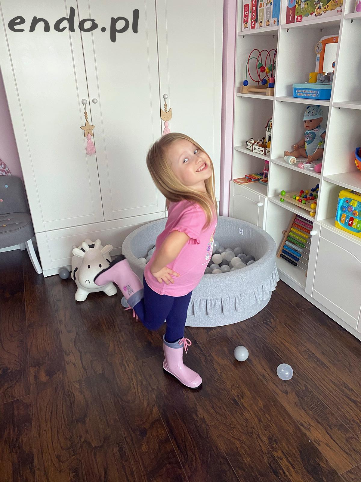 Dziewczynka w domu w różowych kaloszach
