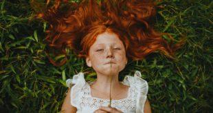 ruda dziewczynka leżąca na trawie