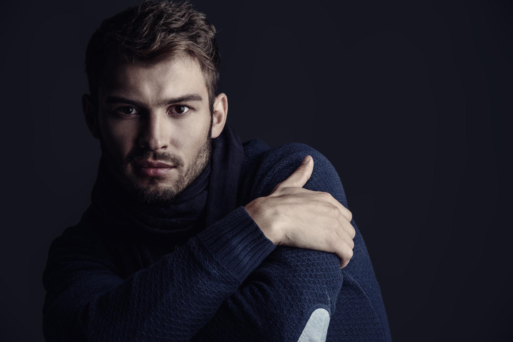 mężczyzna w ciemnym swetrze