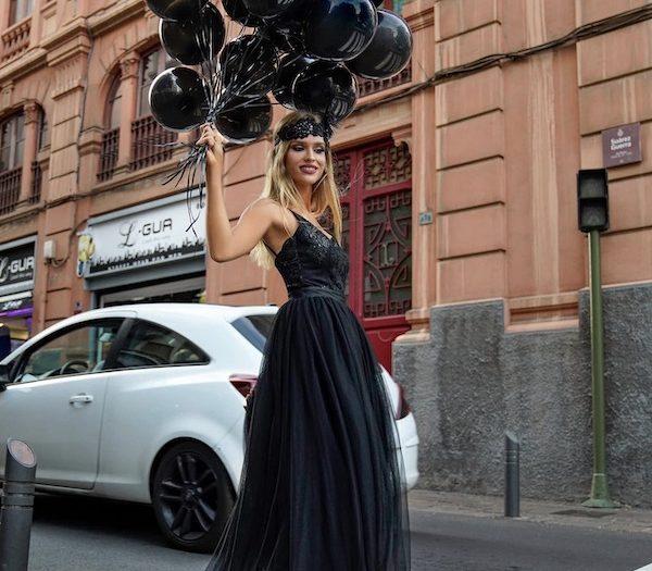 kobieta w czarnej sukience z czarnymi balonami w ręku