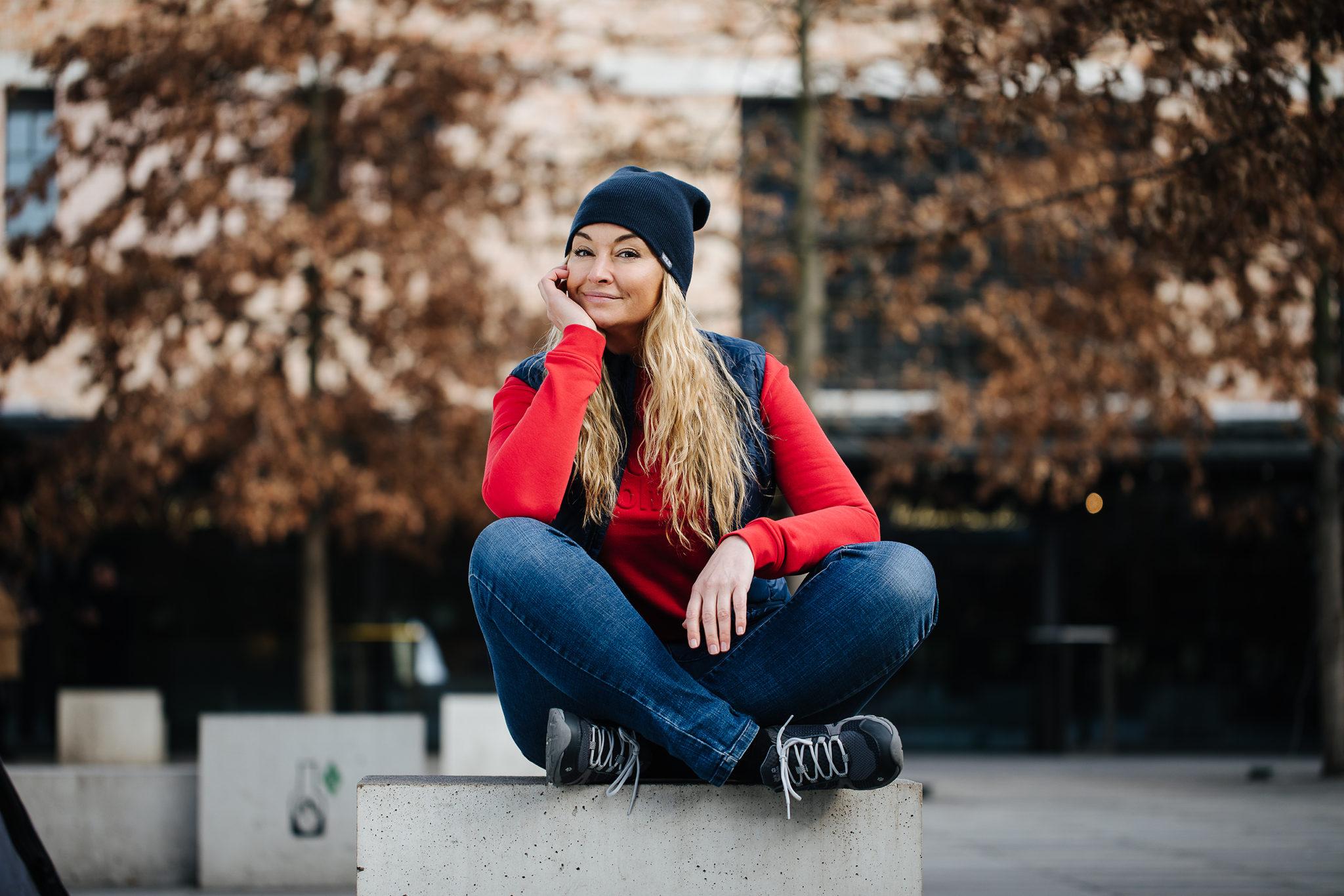 Martyna Wojciechowska w odzieży sportowej siedząca na betonowej ławce
