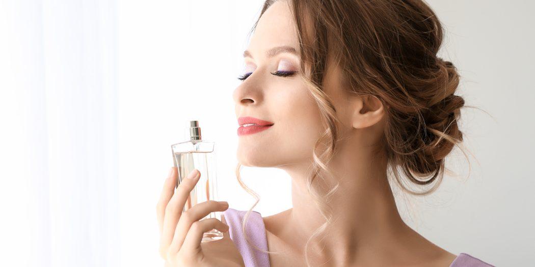piękna kobieta trzymająca perfumy w dłoniach