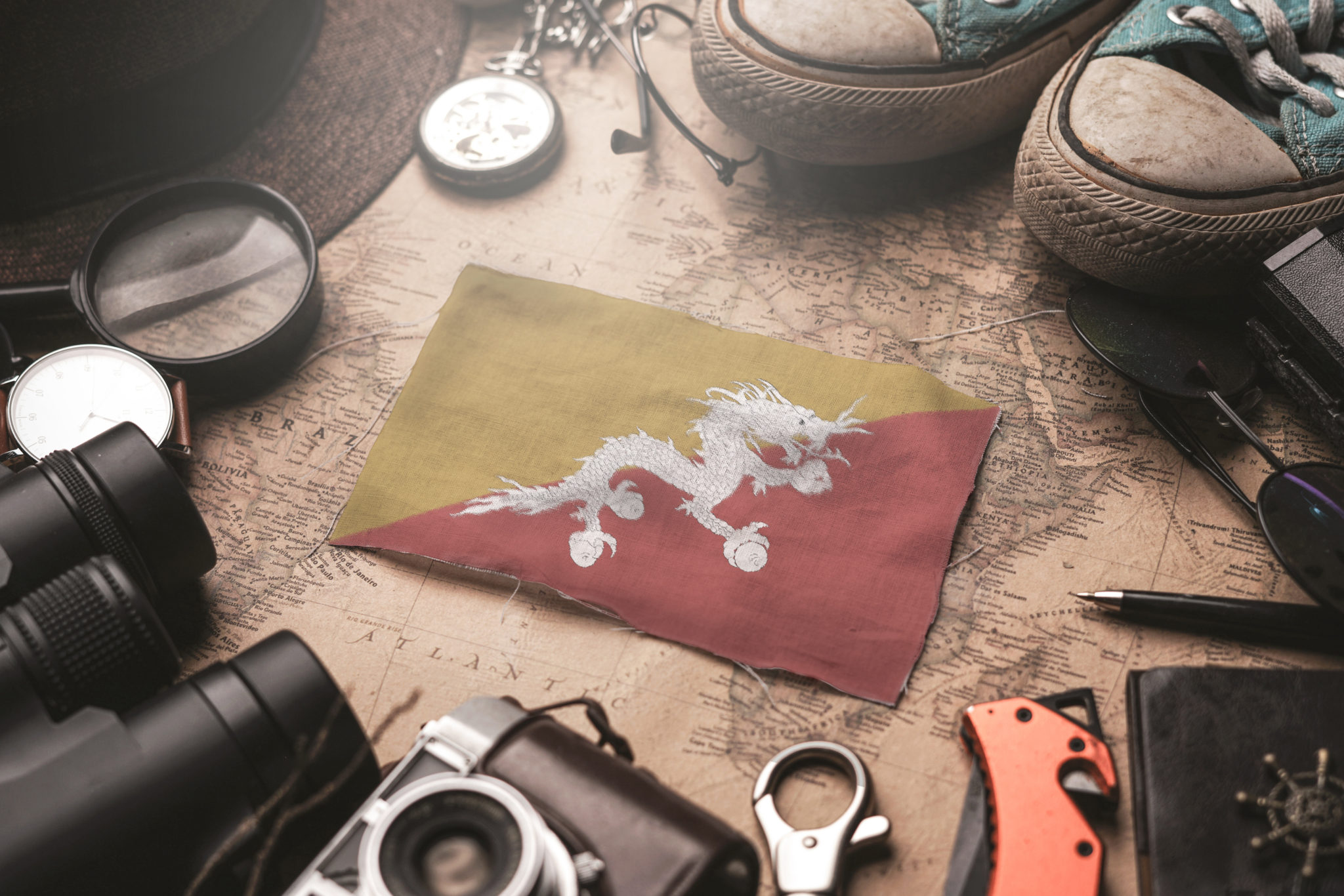 flaga Buthanu, dookoła niej ułożone akcesoria podróżnika