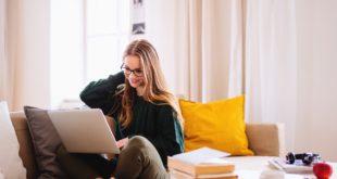 młoda dziewczyna siedząca z laptopem na kanapie