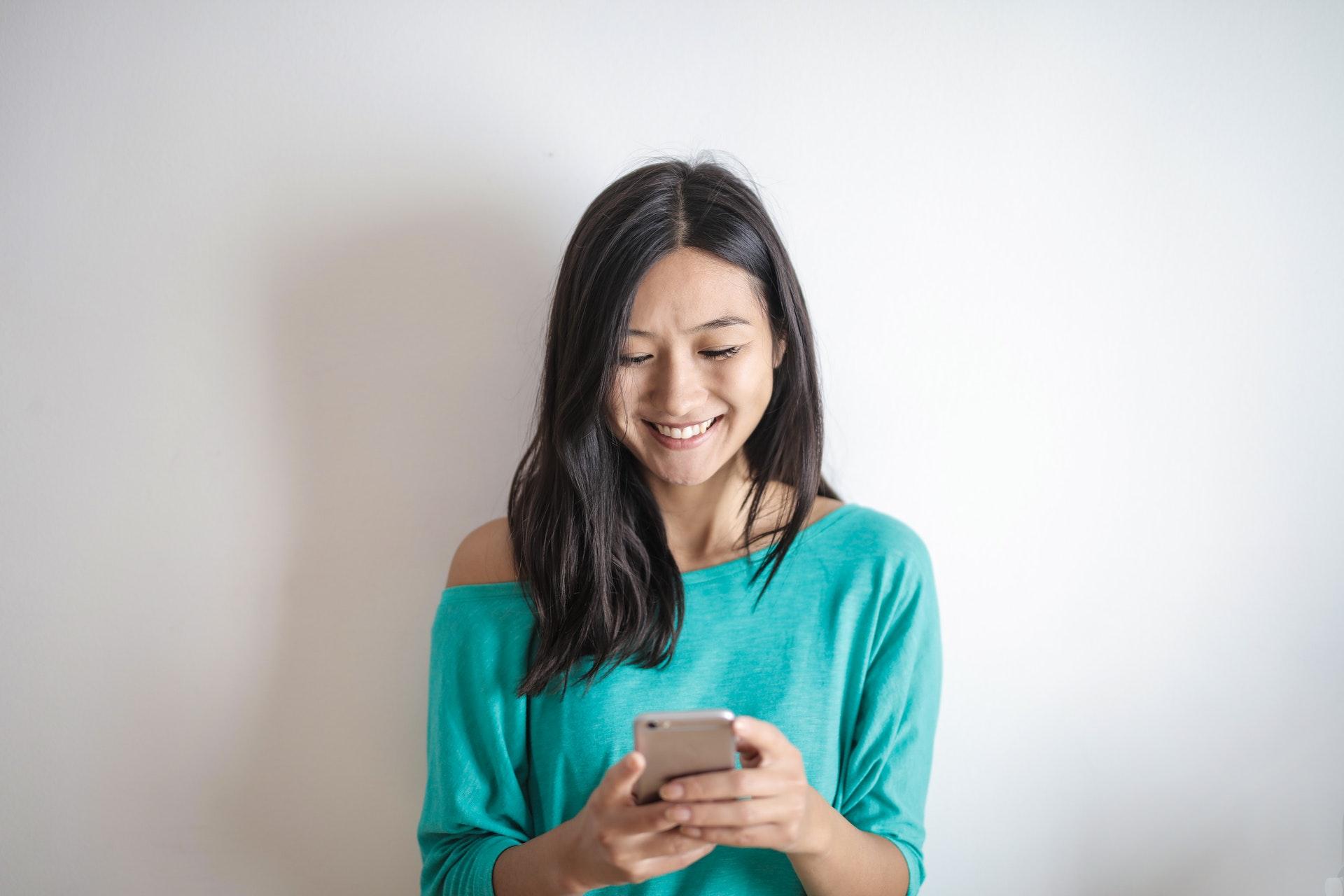 kobieta w zielonej bluzce ze smartfonem