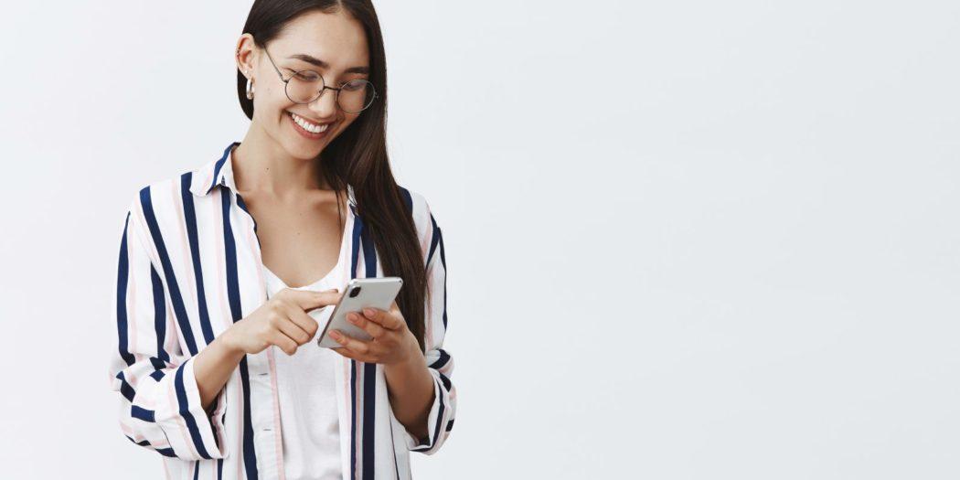 ładna dziewczyna w koszuli w paski ze smartfonem