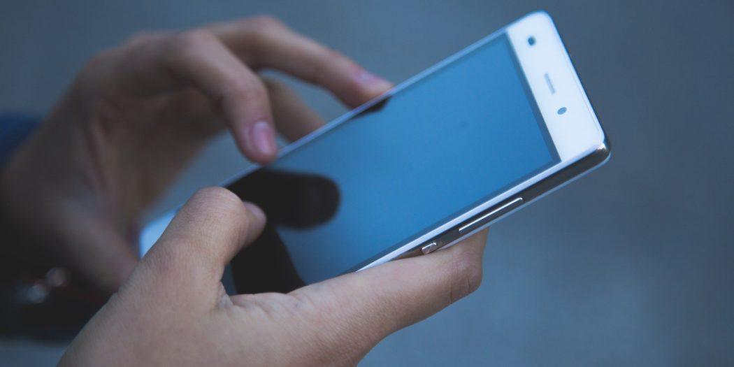 dłonie trzymające smartfona