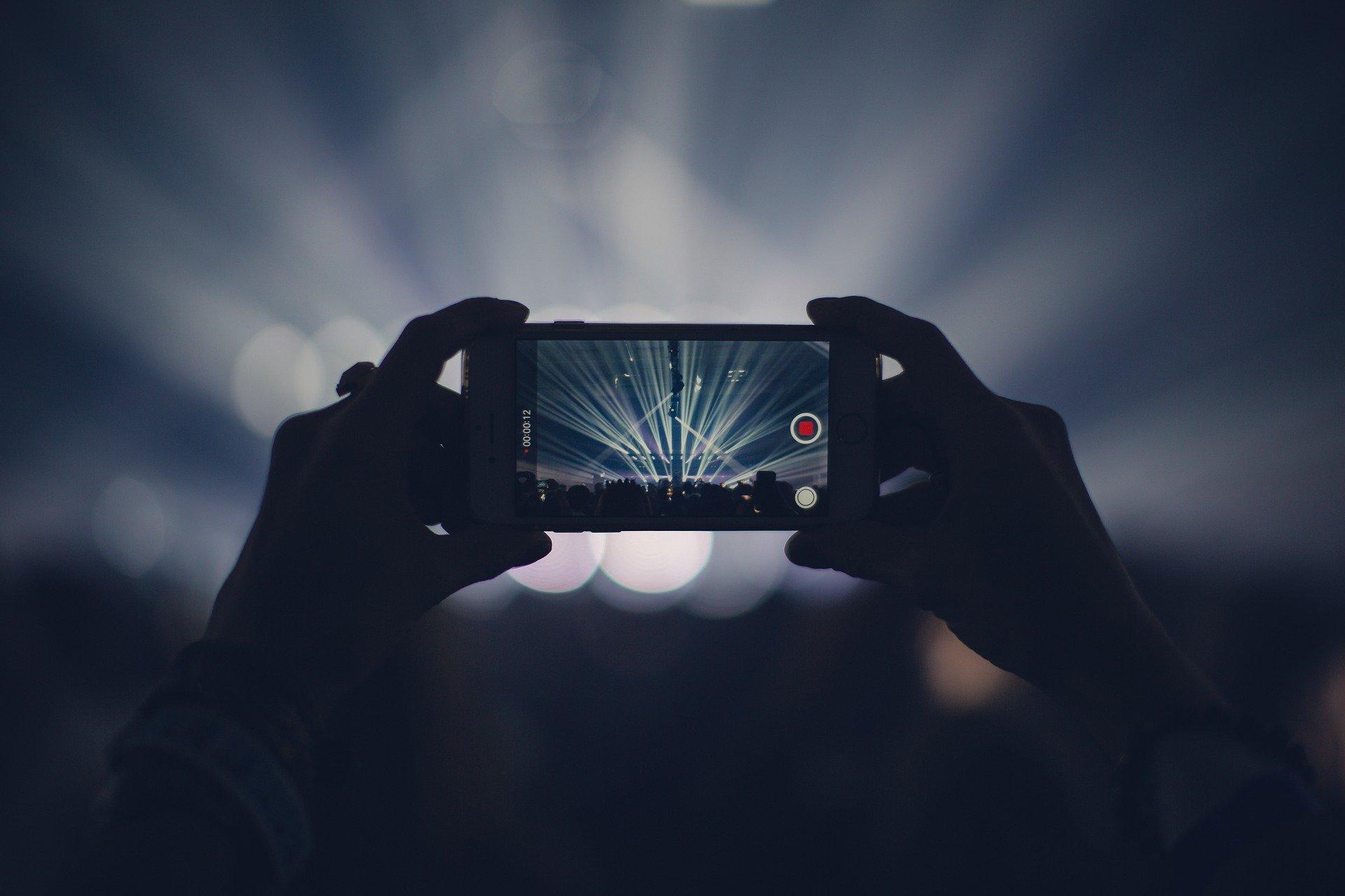 zbliżenie na kobiece dłonie trzymające smartfona do zdjęcia