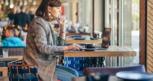 młoda kobieta pracująca na laptopie w kawiarni
