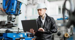 Mężczyzna kontroluje pracę robotów