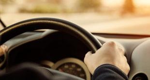 męskie dłonie na kierownicy jadącego samochodu