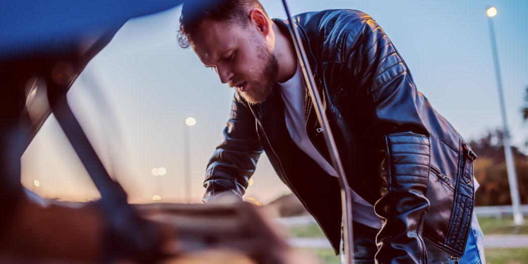 młody mężczyzna nad otwartą klapą samochodu