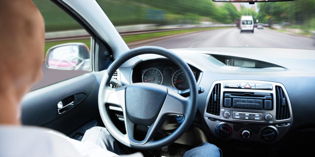 mężczyzna siedzący za kierownicą autonomicznego samochodu