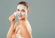 kobieta z maską kremem na twarzy i wacikiem w dłoni