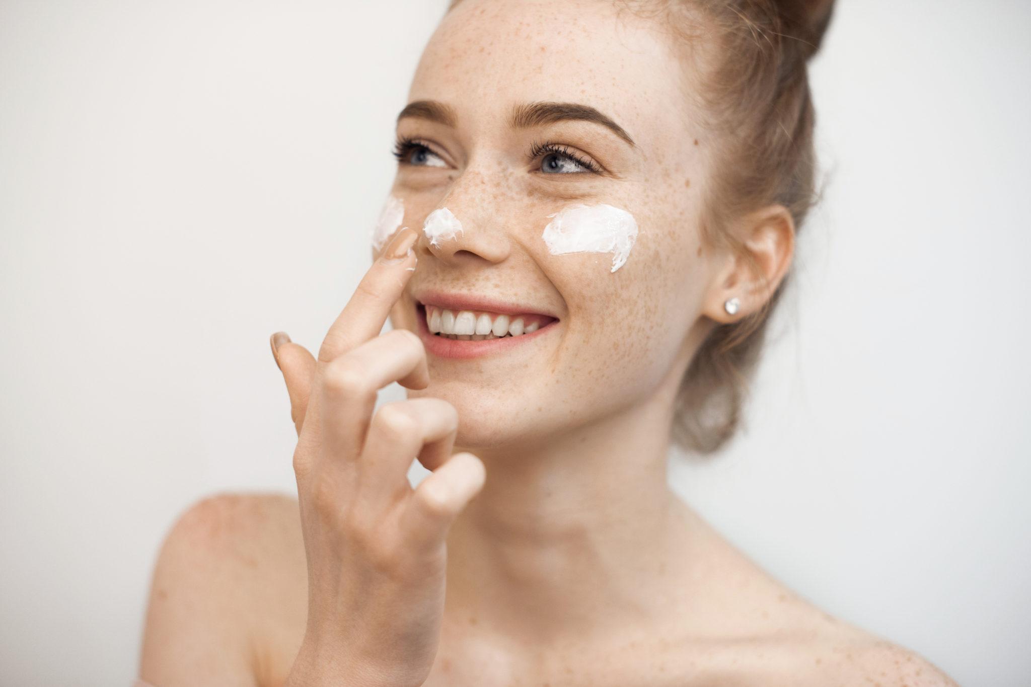 kobieta z piegami wklepująca krem do twarzy