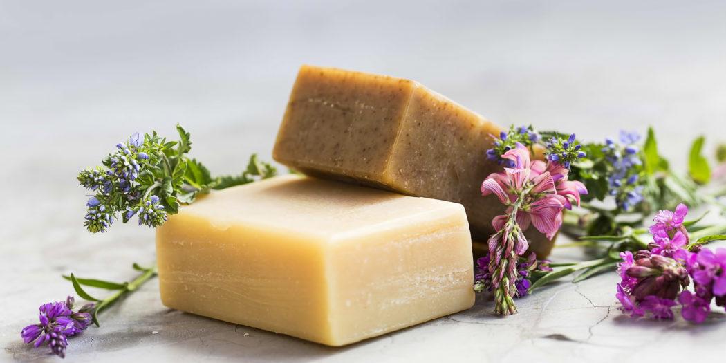 kostki naturalnych mydeł obok ziół i kwiatów