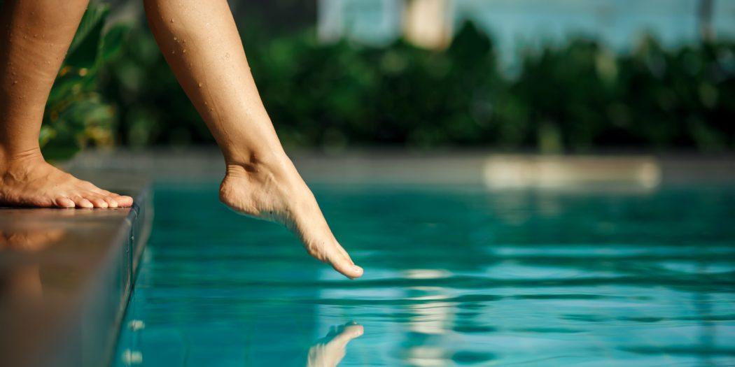 zbliżenie na kobiece stopy dotykające wody w basenie