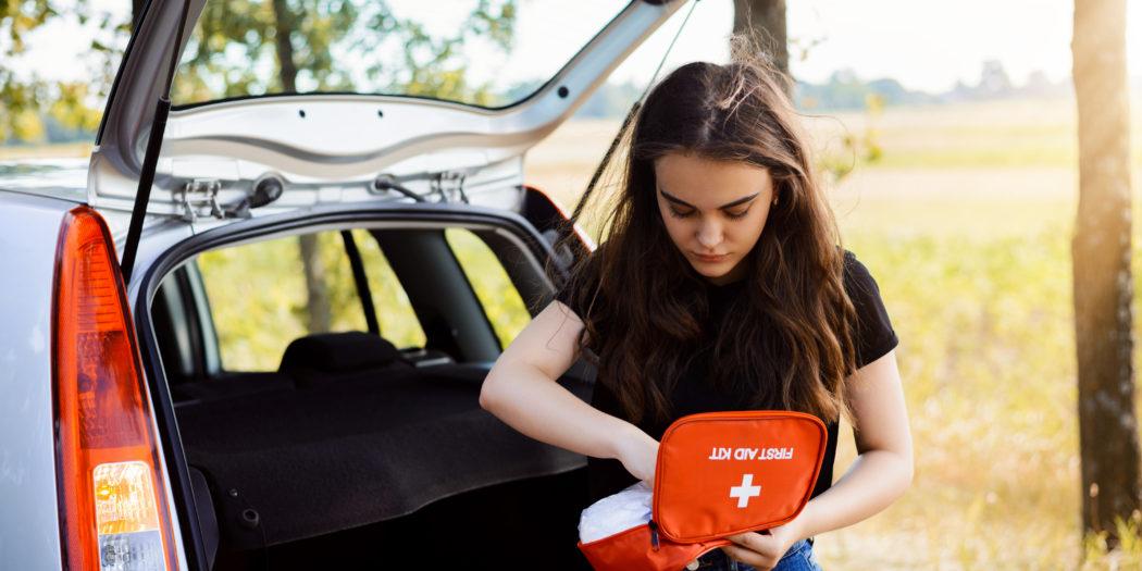 dziewczyna wyjmująca leki z apteczki medycznej z samochodu