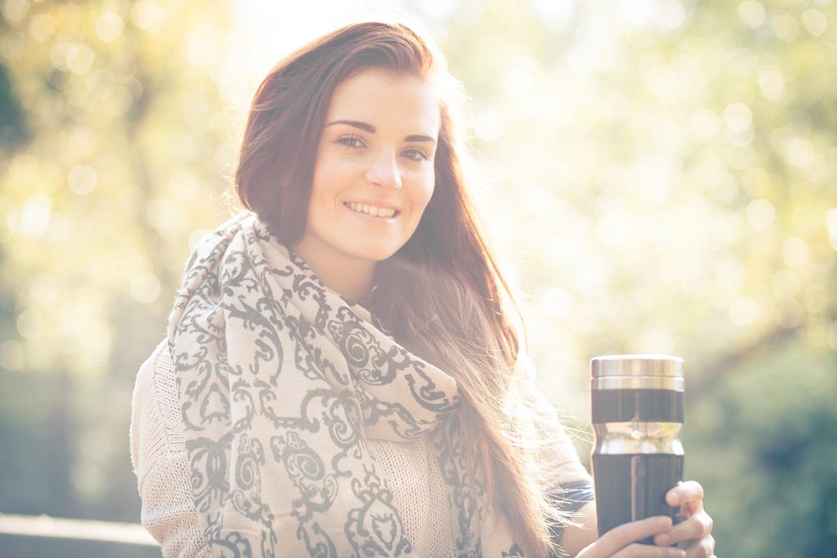 Uśmiechnięta kobieta z kubkiem termicznym